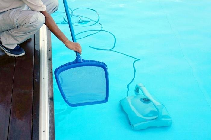 Woman Skimming the pool water