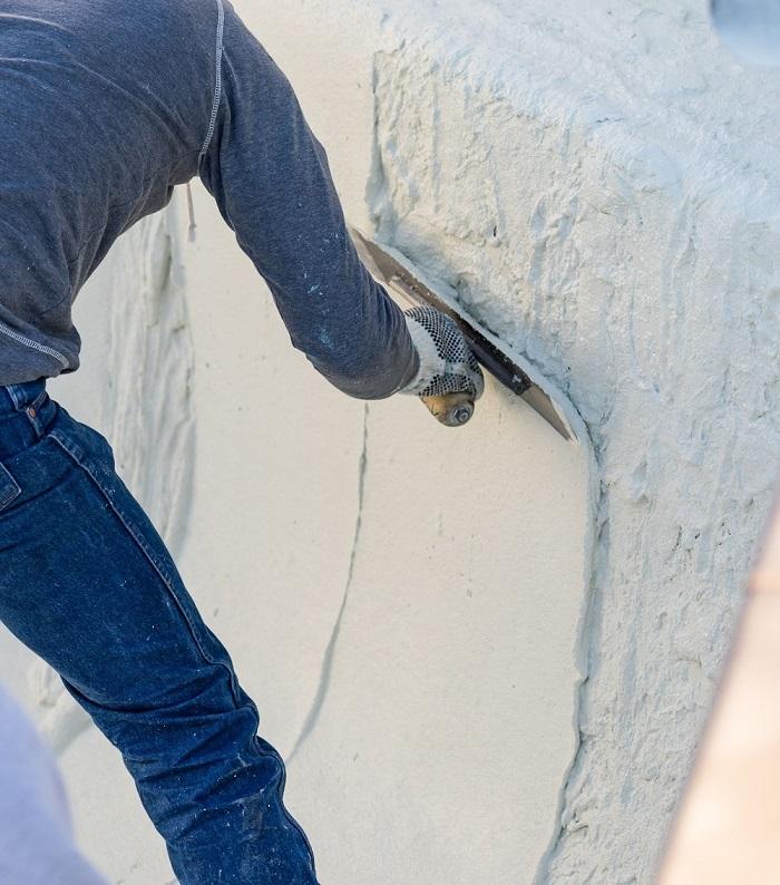 Man applying pool plaster with trowel