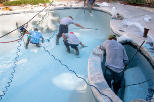 concrete contractors repairing and resurfacing a pool